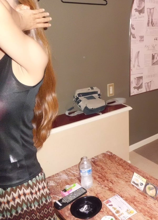 ホテルの部屋で髪をかき上げるシングルマザー